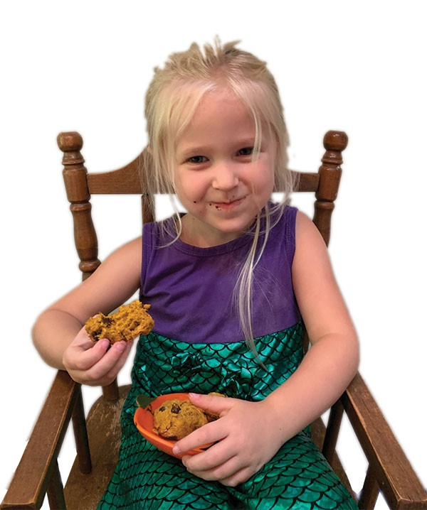 Smiling blonde girl in a chair eating cookies