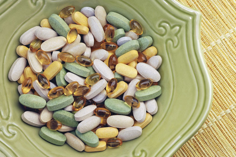 Big pile of vitamins in a green bowl