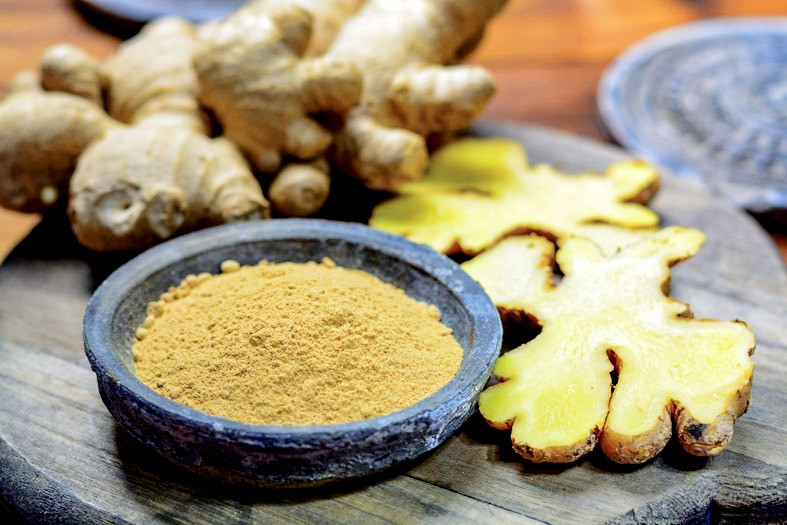 Bowl of ground ginger next to sliced ginger and whole roots