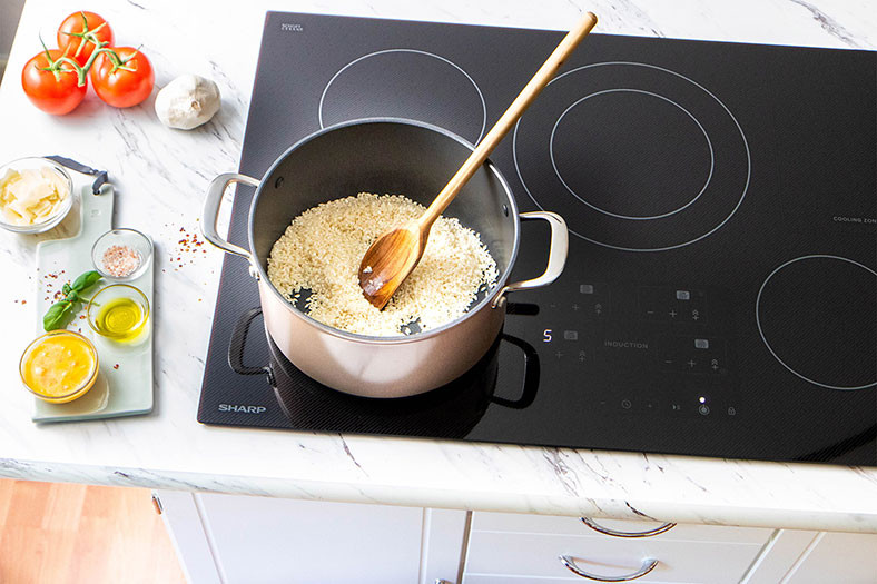 pot of rice site on an induction cooktop next to veg and seasonings