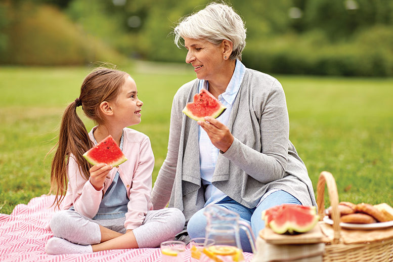 older woman and kid eating watermelon outside