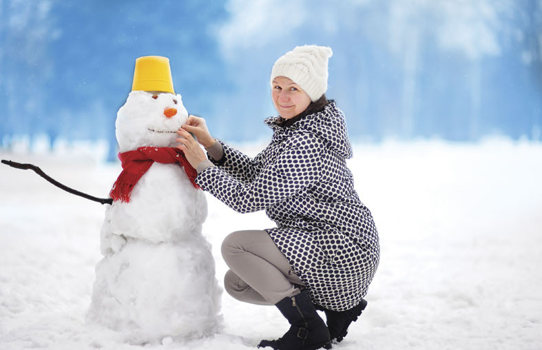 Snow scene with woman squatting down to make a snowman