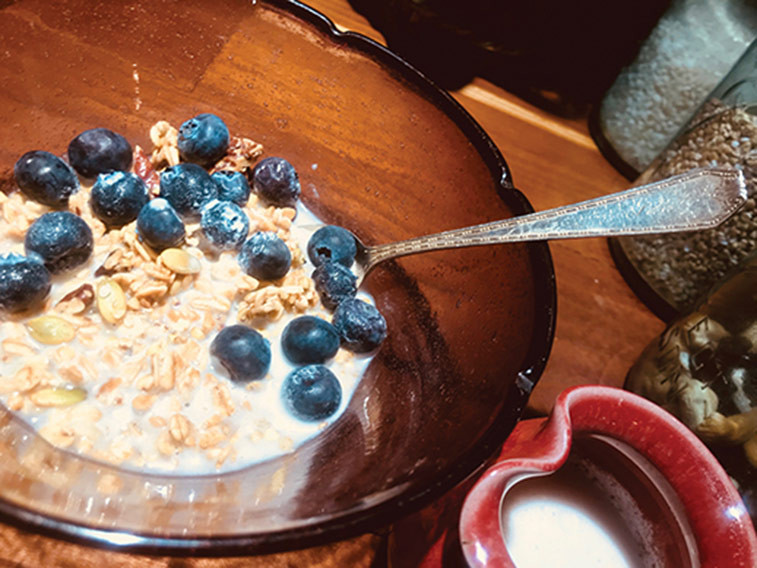 blueberries, milk and granola in a bowl for breakfast
