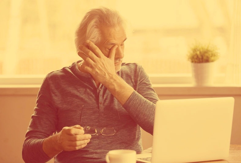 man working on computer rubbing at discomfort in his eyes