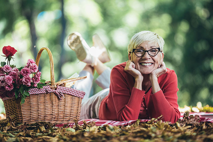 older woman lying on the ground on a picnic blanket