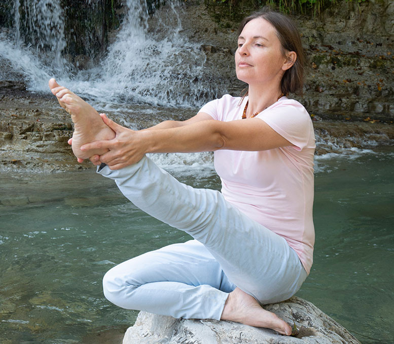 yoga pose woman stretching her leg outside near waterfall