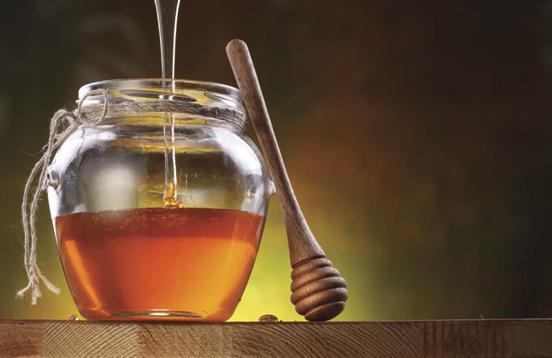 Close up of honey pouring into a jar