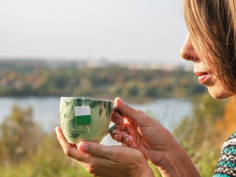 woman relaxes taking time to enjoy a cup of tea destress