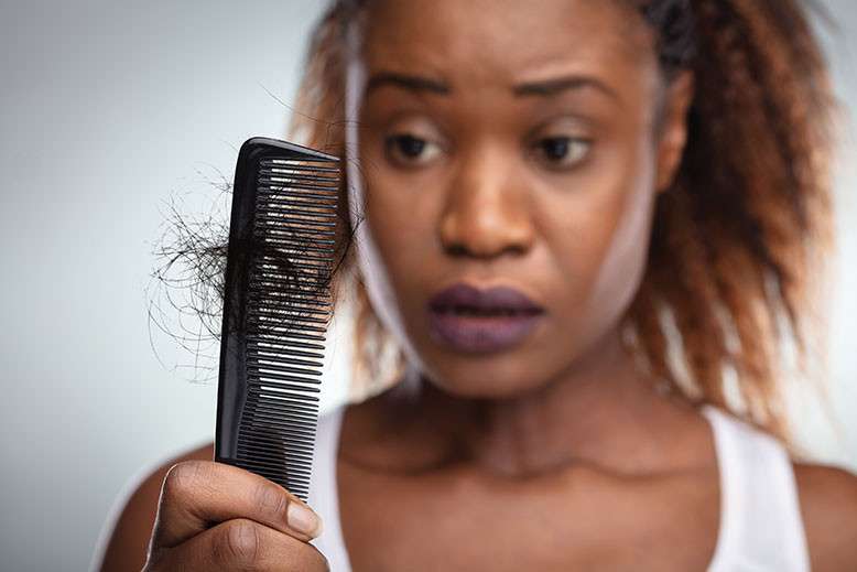 Concerned black woman stares at lost hair in her comb