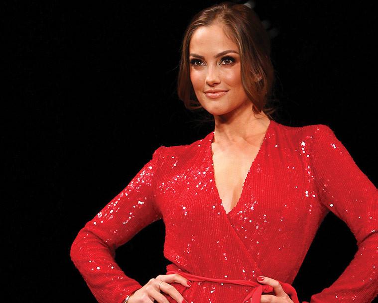 model poses in red dress against stark black background