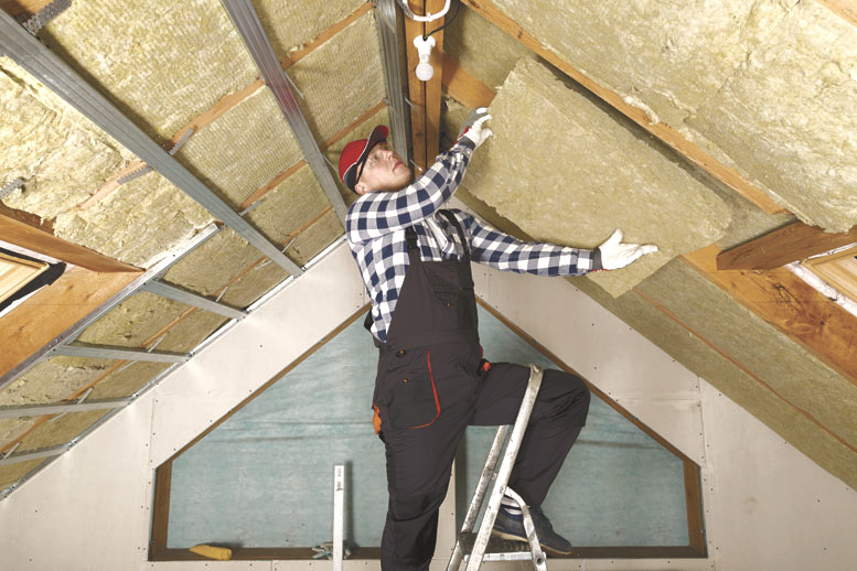 man on a ladder installing pieces of ceiling insulation