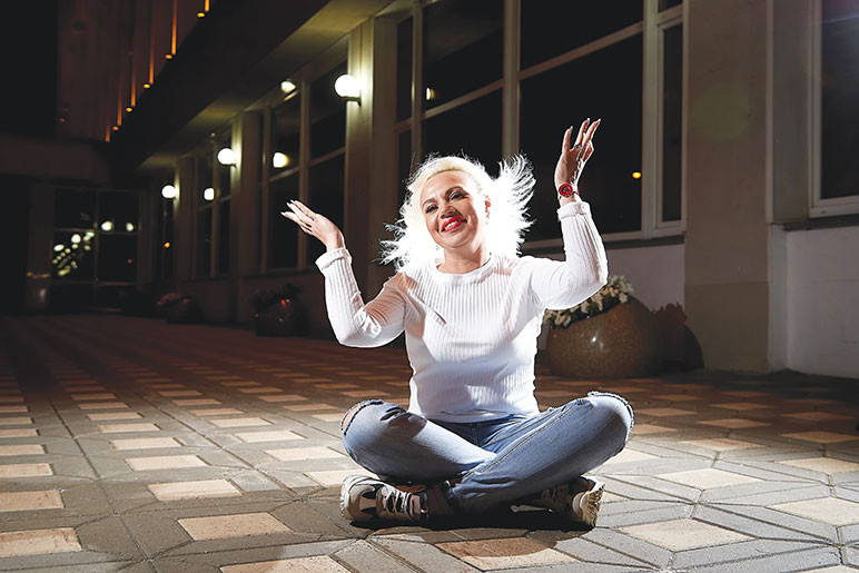 Woman sits in the middle of a sidewalk her hair flying around her head