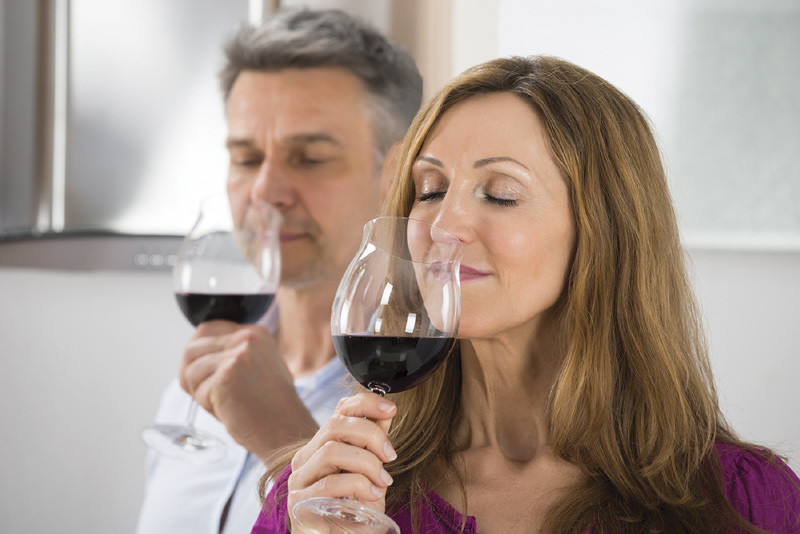 Couple sniffing wine from glasses