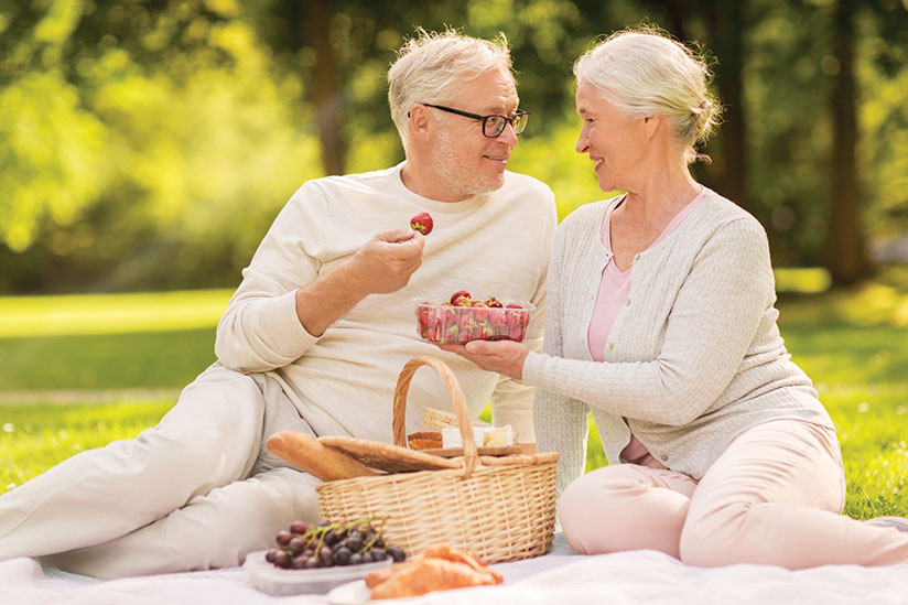 two older white people sharing strawberries fresh fruit
