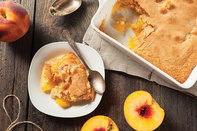 pan of peach cobbler and serving on a plate
