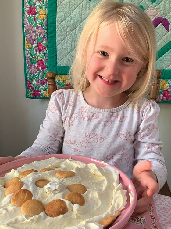smiling blond girl child holding a bowl of banana pudding
