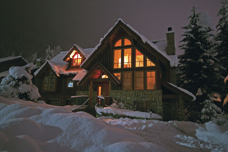 Cold winter Night shot of house lit from inside surrounded by snow
