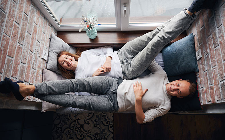 couple relaxing on window seat smiling at the camera