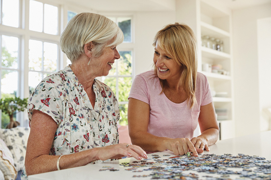 Two women work on a jigsaw puzzle