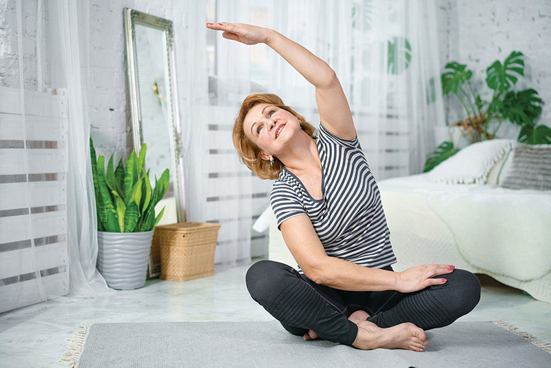 woman on yoga mat stretching