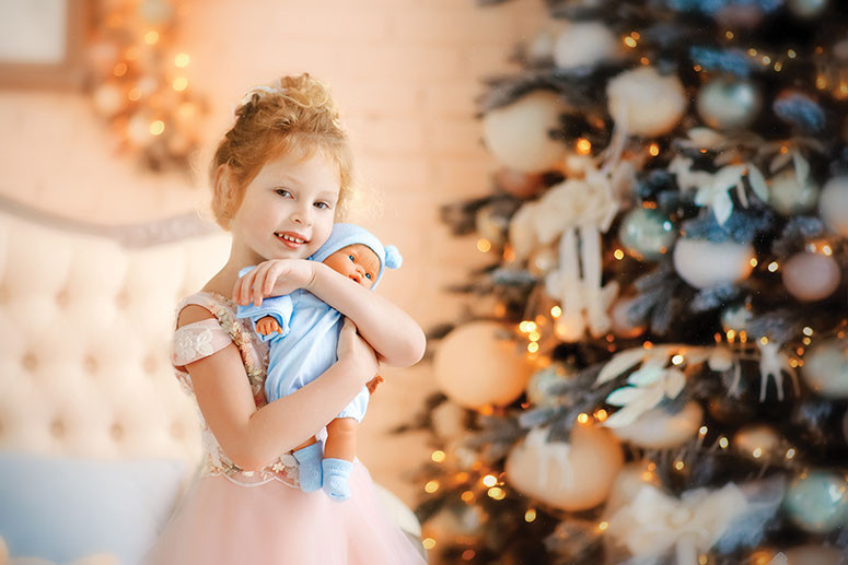 little girl in front of a Christmas tree hugging a doll