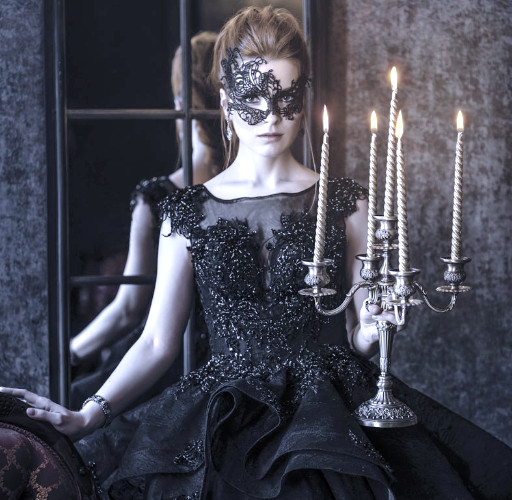 woman in a mask wearing black dress in front of a mirror holding candles
