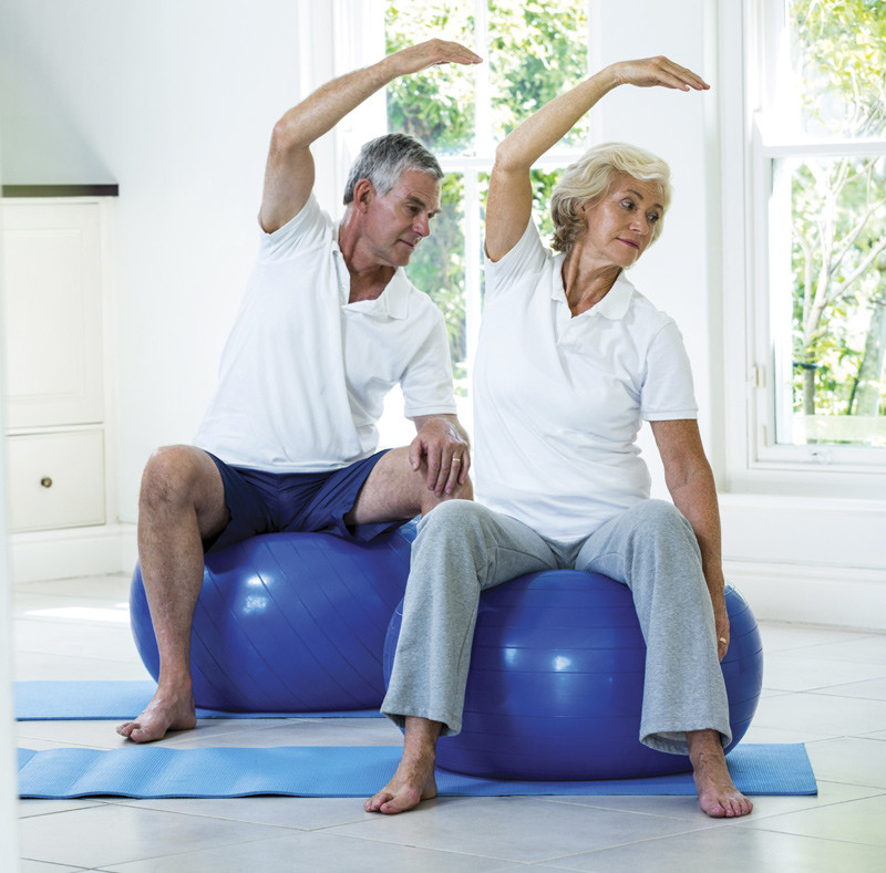 Older couple stretch on exercise balls