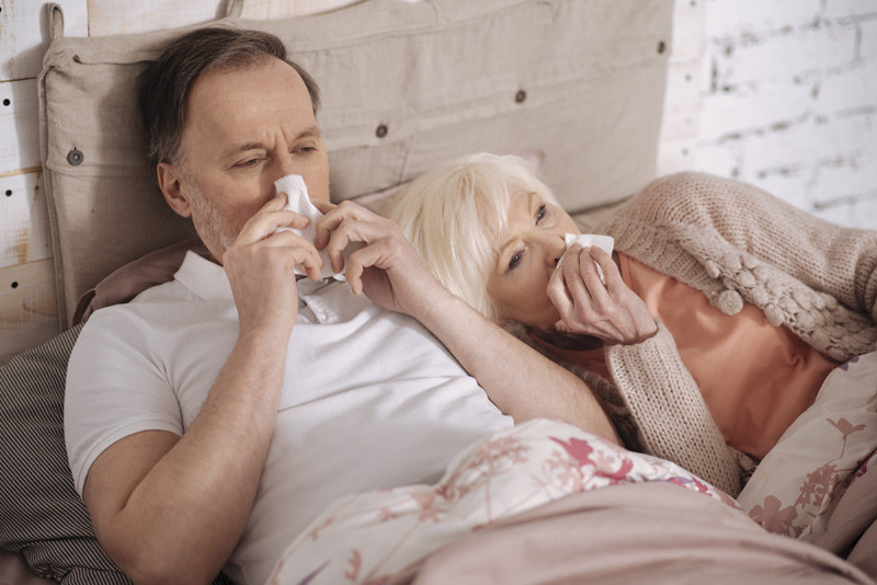 Couple in bed nursing a cold