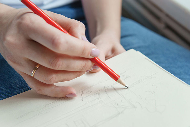 hand holding a pencil to paper and drawing