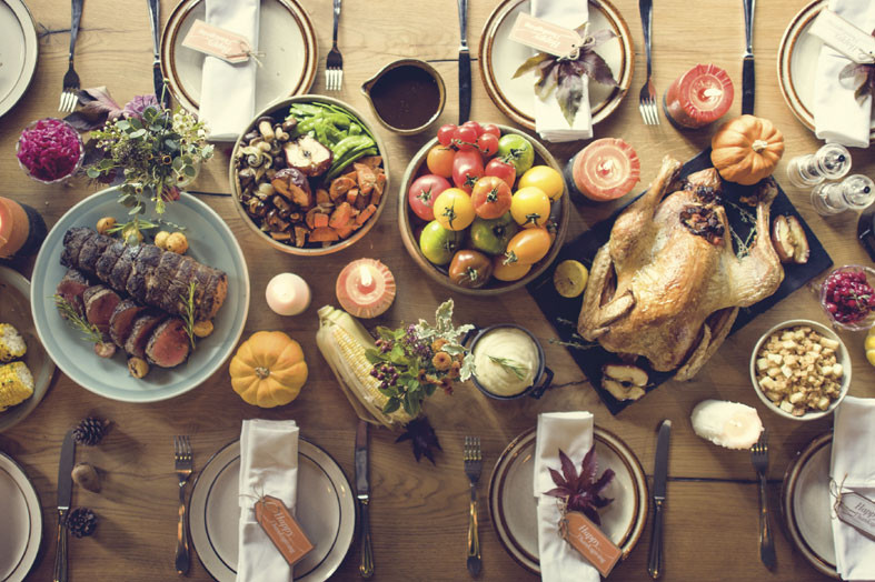 turkey, dressing, salads and other traditional foods laid out on a table for a thanksgiving dinner