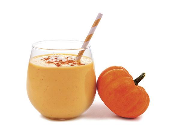 glass of pumpkin milkshake with a small pumpkin next to it