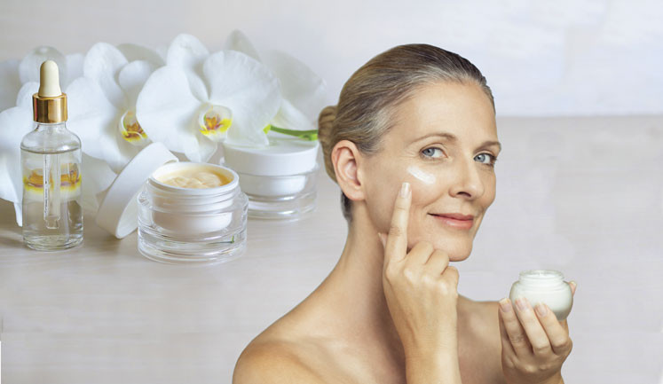 older woman smooths skin cream into her face skin care