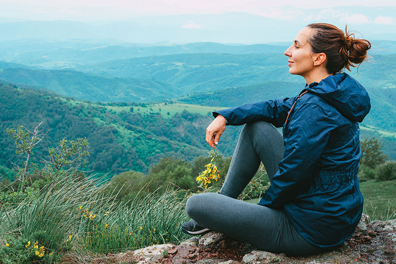 woman at peace sitting on a hilltop enjoying the view