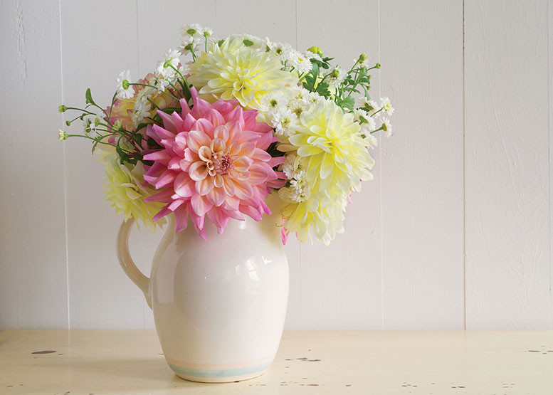 white pitcher vase filled with a colorful floral arrangement