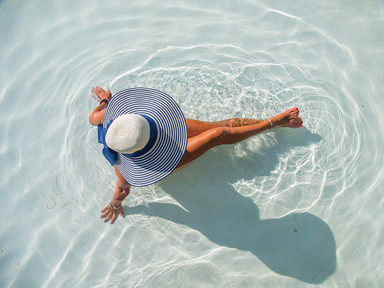 Woman sitting in a pool wearing a wide-brimmed had