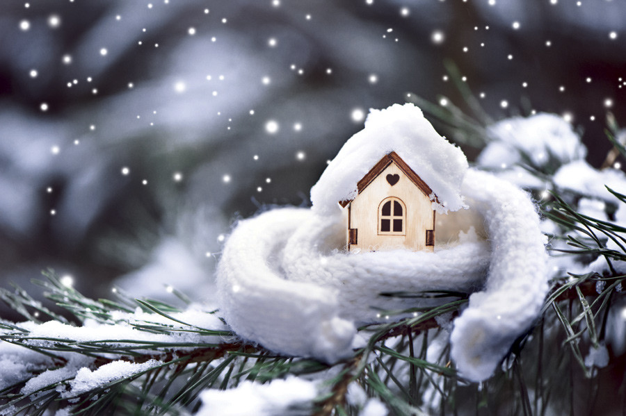 house wrapped in a scarf as snow falls