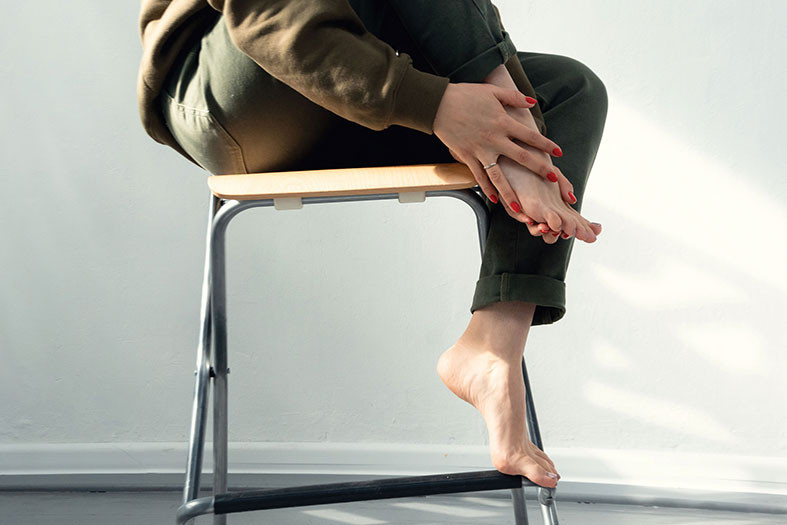 woman massages her foot to reduce swelling