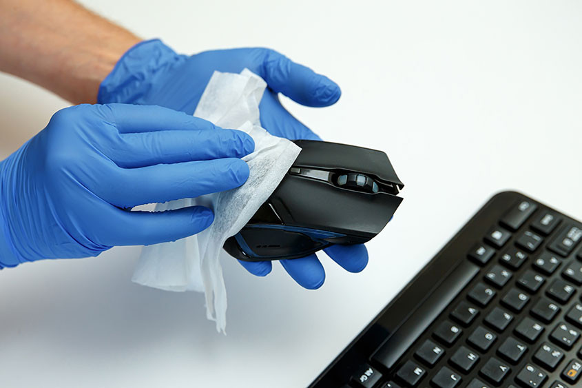 Blue gloved hands disinfect a mouse and keyboard
