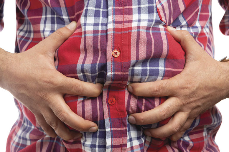 man grabs his stomach because he's bloated for one of these reasons