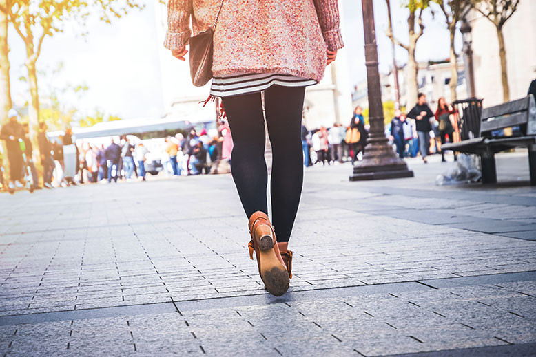 woman dressed well walking along the street wearing heels