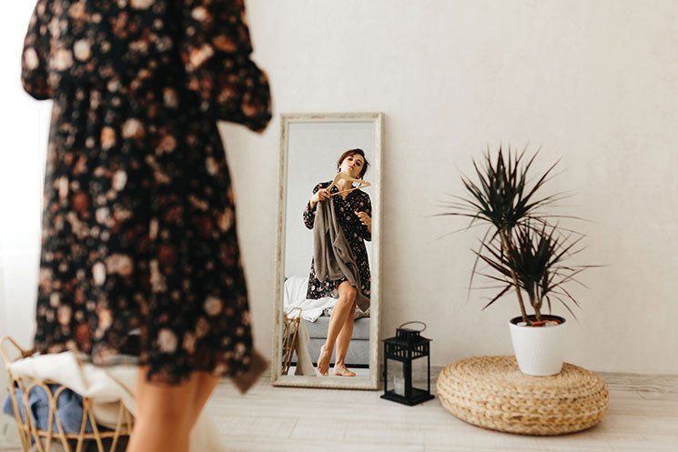 woman trying on dresses in front of a mirror