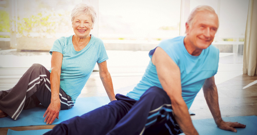 older couple stretching in Yoga class