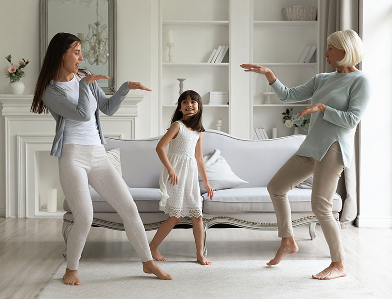 well-dressed multi generations of women dancing in upscale residence