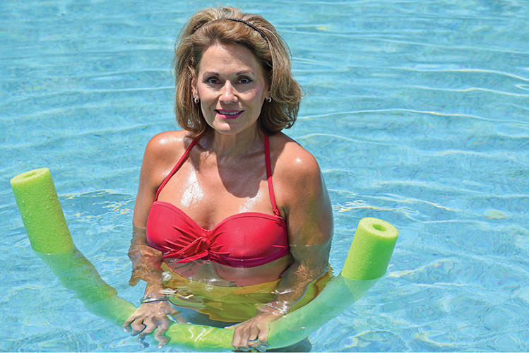 older woman stares at camera in red swinsuit in a pool