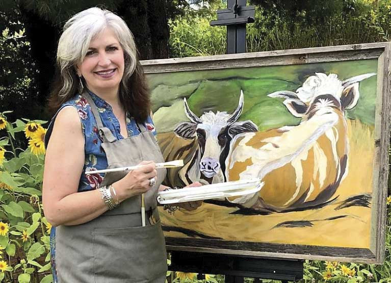 Woman at canvas paints cows