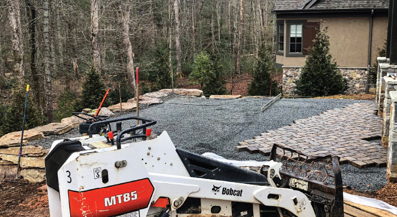Bobcat machinery parked near stone paver project in  patio