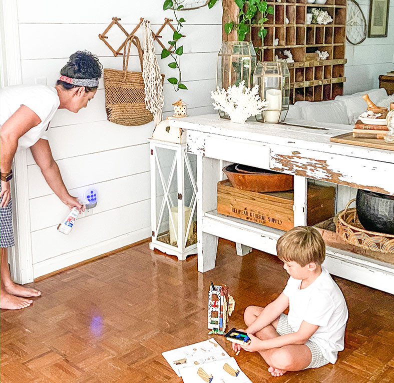 mother sprays for insects while son plays on the floor