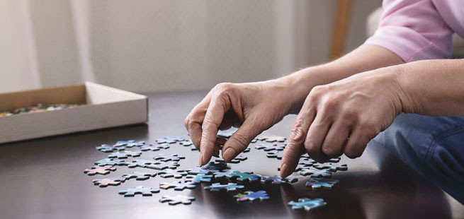 hands working on jigsaw puzzle