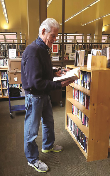 older man peruses a library book
