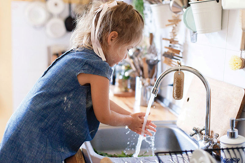 child at the sink washing her hands
